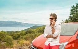人& x28; tourist& x29;在汽车前面谈话在手机 图库摄影