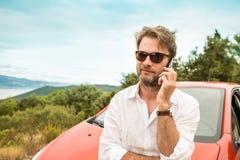 人& x28; tourist& x29;在汽车前面谈话在手机 库存照片