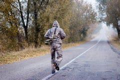 人Backview跑秋天的伪装的 库存图片
