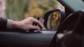 人s手特写镜头视图拿着信用卡的坐在汽车里面,等待支付 影视素材