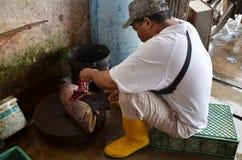 人slaughts卖的一条新近地捉住鱼对顾客 图库摄影