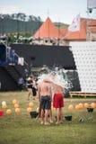 人spours从在他的朋友头的一个桶浇灌 图库摄影