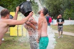 人spours从在他的朋友头的一个桶浇灌 免版税库存照片