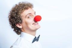 年轻人studen或与一个红色小丑鼻子的商人。 免版税库存照片