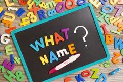 什么对黑板的名字对于一个新的婴孩,问题有许多五颜六色的塑料信件的和正面妊娠试验 库存照片
