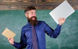 什么您将更喜欢 老师有胡子的行家拿着书和膝上型计算机 选择现代教学方法的老师 纸 免版税库存图片