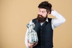 什么是投资金钱一个好方式  认为投资的有胡子的人金钱入事务 商人计算 免版税库存图片