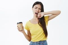 仅咖啡罐与睡眠战斗 打呵欠与闭合眼睛盖的黄色T恤杉的疲乏和困逗人喜爱的女性工友 库存照片