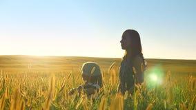 今后指向年轻愉快的母亲谈话与小女儿和,一起坐麦子或黑麦领域,微笑 影视素材