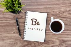 今天激动人心的行情被启发 在笔记本的正面诱导文本,一个杯子早晨无奶咖啡,笔和 图库摄影