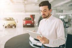 介绍新的汽车的友好的车推销员在陈列室 显示新的汽车的年轻男性顾问照片在车展 库存图片