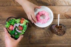 介绍选择吃在油炸圈饼和沙拉之间 免版税库存图片