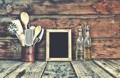 仍然厨房生活 在一个立场的厨房器物在木墙壁附近 厨房工具,与自由空间的木制框架在成套工具的文本的 图库摄影