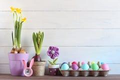 仍然复活节生活 上色鸡蛋,有兔子的耳朵的,在罐的春天花手表 免版税库存图片