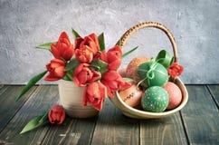 仍然复活节生活 红色郁金香和红色和绿色东部篮子  免版税图库摄影