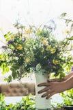 仍然生活夏天 舒适家 拿着有夏天花束的女性手花瓶 免版税库存照片