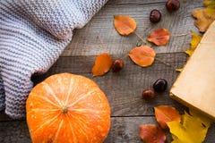 仍然秋天生活 秋叶、温暖的围巾和南瓜在木板 顶视图,葡萄酒样式 免版税库存图片