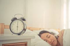 仍然计数对有妇女的六个o时钟的闹钟在床上 库存图片