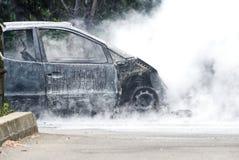 仍然闷燃一辆被烧的汽车的遗骸 库存图片