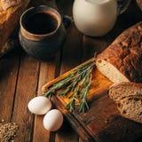 仍然1寿命 农产品:鸡蛋,牛奶,在一张木桌上的新鲜面包 特写镜头一把戏 库存图片