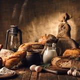 仍然1寿命 农产品:鸡蛋,牛奶,在一张木桌上的新鲜面包 特写镜头一把戏 免版税图库摄影