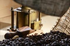 从一个咖啡袋在一个老铜磨咖啡器和小铲的看法从橄榄色的木头的大块产品的 免版税库存图片