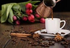 从一个土耳其咖啡罐的倾吐的咖啡通过一杯咖啡 库存图片