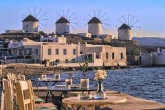 从一个大阳台的Myconos希腊视图在风车的海在日落的一个晴天 明亮的蓝色海和天空 免版税库存照片