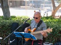 从一个小组的一个吉他弹奏者街道音乐家在特拉维夫,以色列演奏路人的音乐 免版税库存图片