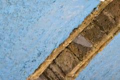 从一个斜角的门道入口做横跨蓝色涂灰泥的墙壁的一条对角线 免版税库存照片