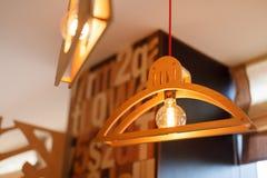 从一个木挂衣架和玻璃灯的两设计师装饰在天花板垂悬 库存照片