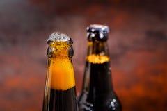 从一个正义被打开的啤酒瓶的啤酒溢出在黑暗的背景 免版税库存照片