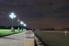从一个灯柱的光在晚上在公园 在Riverwalk,照明设备,就座,晚上逃走风景 免版税库存图片