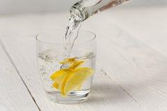 从一个玻璃瓶的倾吐的水到与柠檬切片的一块玻璃里 库存图片