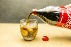 从一个瓶的倾吐的可口可乐到与冰块的一块玻璃里 库存照片