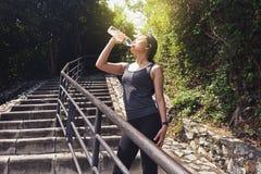 从一个瓶的健身妇女饮用水在跑以后 免版税库存照片