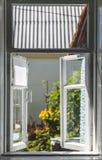 从一个老农村窗口的看法在一个晴朗的夏天庭院里 免版税库存照片