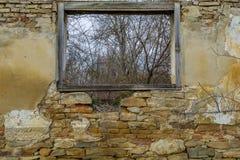从一个老废墟房子的木窗口的看法在森林附近的 免版税库存图片