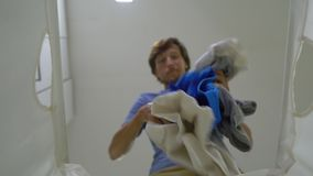 从一个肮脏的洗衣篮的看法怎么在它的一块年轻人投掷肮脏的布料 家务概念 男性做的概念 股票录像