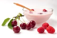 从一个莓和一棵樱桃的酸奶在有一把木匙子的一个玻璃碗 免版税图库摄影