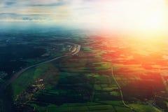 从一个鸟` s眼睛视图的看法到地面,对天际的看法,在领域、河和路,日落下 库存照片