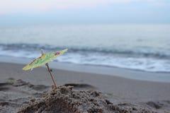 从一个鸡尾酒的一把伞在海滩的沙子以海波浪为背景 库存图片