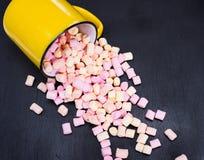 从一个黄色杯子驱散的五颜六色的蛋白软糖 免版税图库摄影