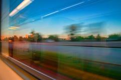 从一列火车的被弄脏的窗口视图在行动 火车移动由铁路,自然外面,被弄脏的光 日落天空和城市 库存图片
