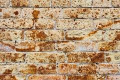 从一块古老黄色葡萄酒砖的背景墙壁与表面上的生锈的腐蚀样式 背景构造了 库存图片