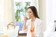 从一块玻璃的妇女饮用水在旅馆客房 免版税图库摄影