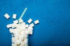 从一块玻璃的溢出的糖在蓝色背景 在每天饮料的巨型糖含量 库存图片