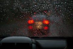 从一块雨被透湿的挡风玻璃的看法在前面的一辆汽车 免版税库存图片