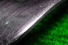 从一把金属匙子的零件的抽象背景在一个绿色宏指令的 库存照片