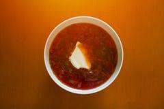 从一棵甜菜的红色甜菜根与切片在一块白色板材的酸性稀奶油在一张木桌上 图库摄影